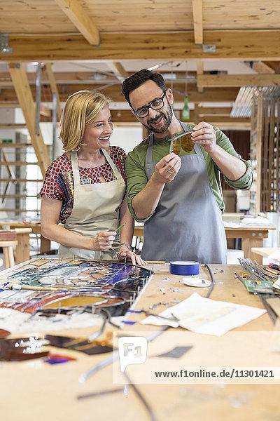 Glasmaler bei der Untersuchung von Glasstücken im Atelier