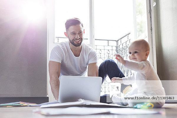 Vater arbeitet am Laptop und sieht zu  wie seine Tochter auf dem Boden spielt.