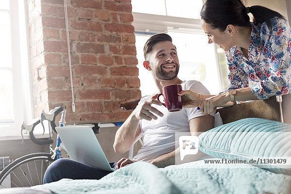Freundin bringt Kaffee zum Freund mit Laptop im Schlafzimmer