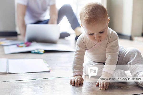 Baby Tochter sitzt auf dem Boden in der Nähe von Vater arbeitet am Laptop