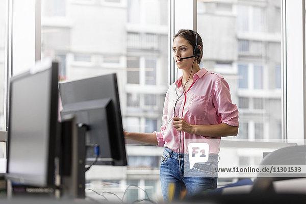 Geschäftsfrau am Telefon mit Freisprecheinrichtung im Büro