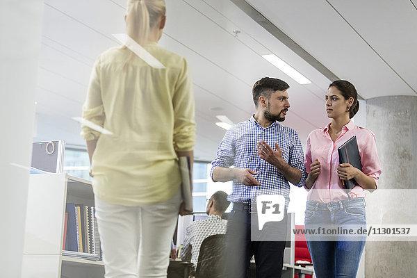 Geschäftsleute beim Reden und Gehen im Büro