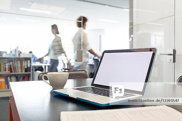 Laptop und Kaffeetasse auf dem Schreibtisch mit Geschäftsleuten im Hintergrund