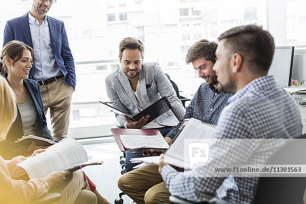 Geschäftsleute bei der Überprüfung und Besprechung von Papierkram-Meetings im Büro