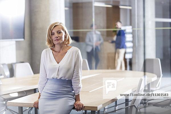 Porträt einer selbstbewussten Geschäftsfrau am Konferenztisch
