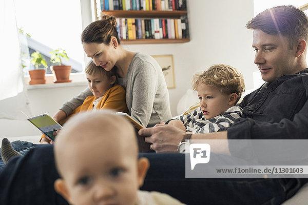 Familie liest Bilderbücher im Schlafzimmer zu Hause