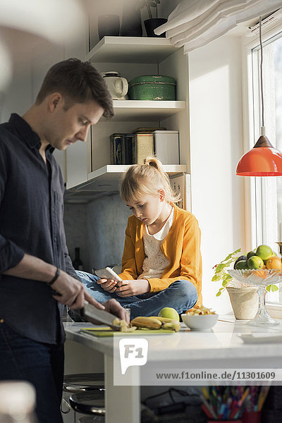 Vater schneidet Früchte weißes Mädchen mit dem Handy in der Küche