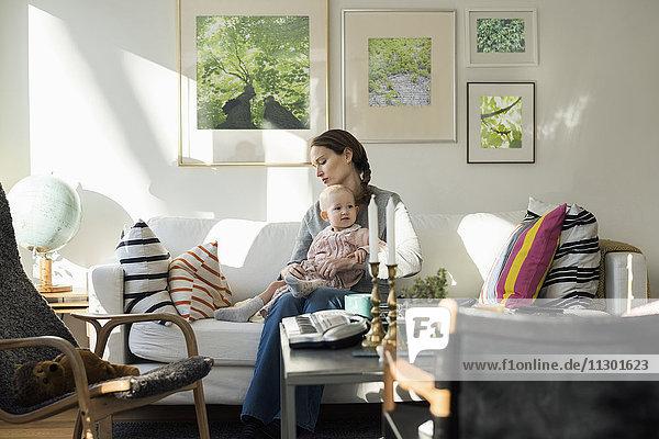 Frau sitzend mit Mädchen auf dem Sofa zu Hause