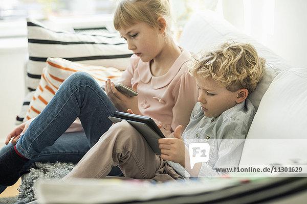 Geschwister mit Technologien auf dem Sofa zu Hause