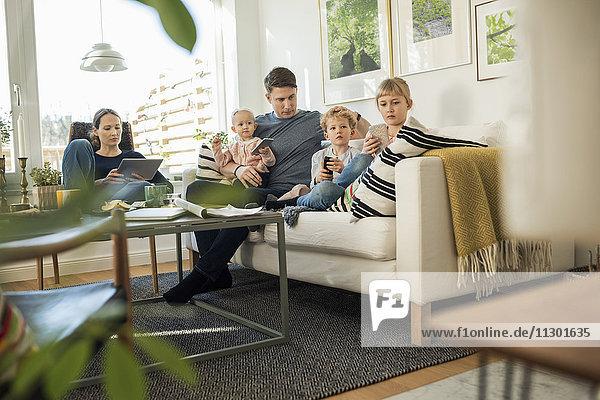 Familie sitzt zu Hause auf dem Sofa