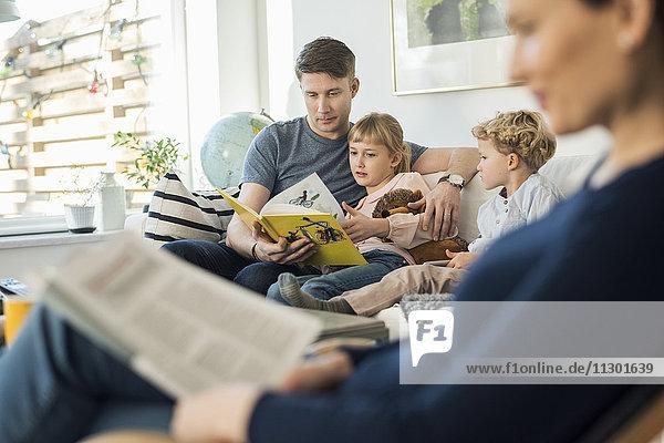 Vater liest Geschichtenbuch für Kinder mit Mutter im Wohnzimmer