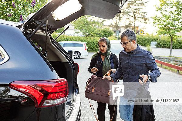 Mann und Frau halten Gepäck im Kofferraum  während sie am Straßenrand stehen.