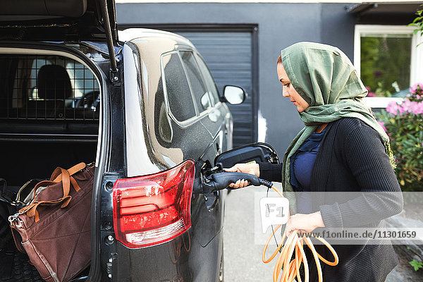 Seitenansicht der Frau  die ein Elektroauto mit offenem Kofferraum lädt  während sie vor dem Haus steht.