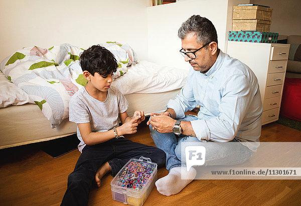Vater und Sohn spielen mit Gummibändern  während sie zu Hause auf dem Parkettboden sitzen.