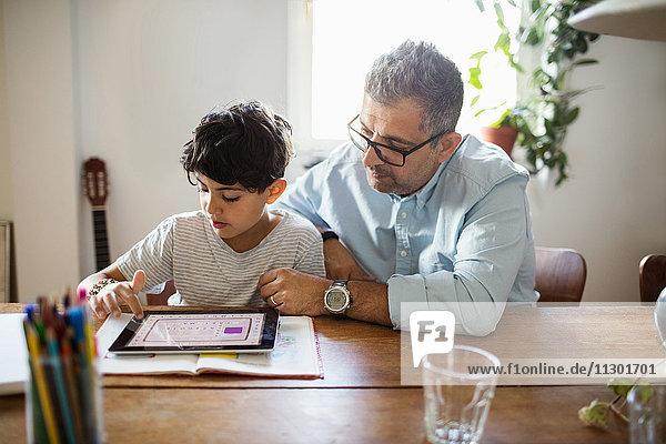 Vater unterstützt den Sohn bei der Verwendung des digitalen Tabletts zu Hause