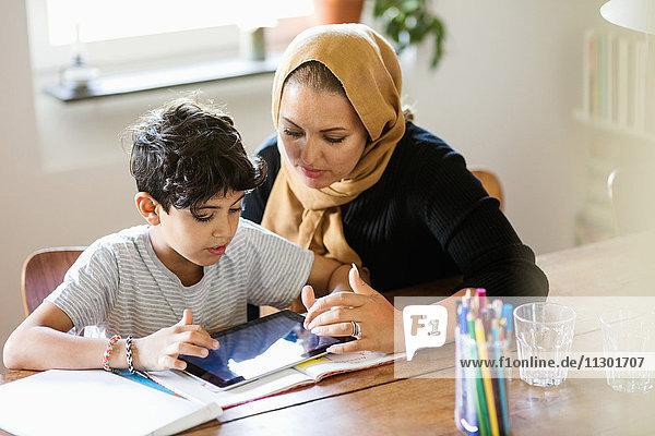 Mutter und Sohn beim Lernen zu Hause mit dem digitalen Tablett