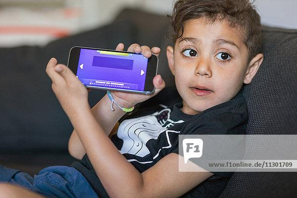 Junge zeigt Spiel auf dem Smartphone-Bildschirm zu Hause an