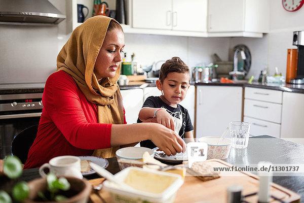 Mutter und Sohn beim Frühstück am Esstisch in der Küche