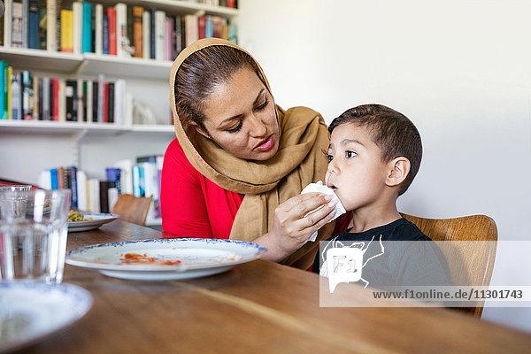 Mutter wischt den Mund des Sohnes nach dem Mittagessen am Esstisch.