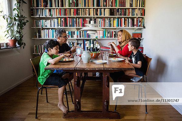 Familie beim Essen am Tisch im Bücherregal