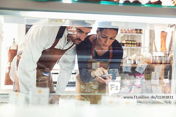 Besitzer und Besitzerinnen von Smartphones bei der Untersuchung der Vitrine im Lebensmittelgeschäft