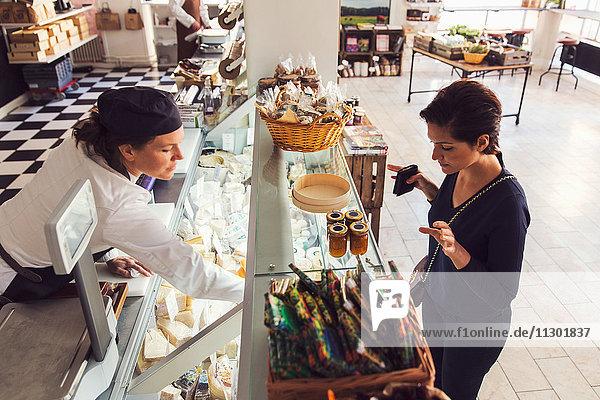 Hochwinkelansicht der Frau  die Lebensmittel von der Verkäuferin im Geschäft kauft.