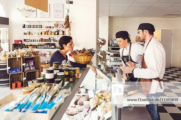 Seitenansicht der Frau  die Lebensmittel von den Eigentümern im Geschäft kauft.