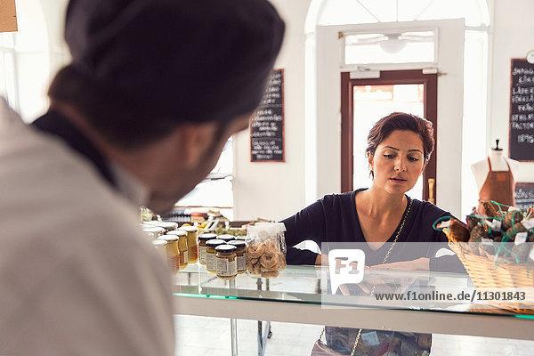 Frau kauft Lebensmittel vom männlichen Besitzer im Laden