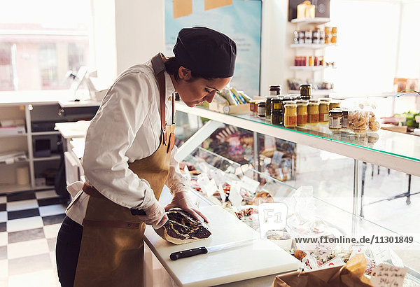 Besitzerin beim Schneiden von Fleisch am Tresen im Lebensmittelgeschäft