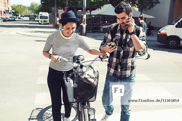 Mann mit Smartphone beim Gehen mit Frau auf der Straße