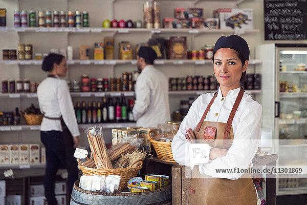 Portrait eines selbstbewussten Besitzers  der die Arme verschränkt  während Kollegen im Lebensmittelgeschäft arbeiten.