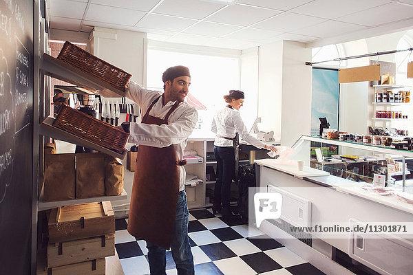 Männlicher Besitzer schaut weg  während er in einem hell erleuchteten Lebensmittelgeschäft steht.