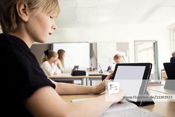 Junge lernen durch digitales Tablett im Klassenzimmer