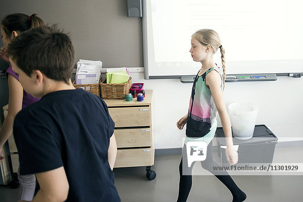 Schulkinder  die im Klassenzimmer gegen das Whiteboard laufen
