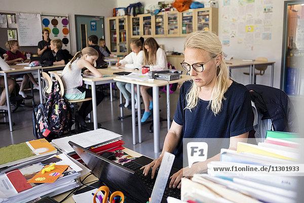 Lehrer mit Laptop auf dem Schreibtisch mit Schülern im Klassenzimmer