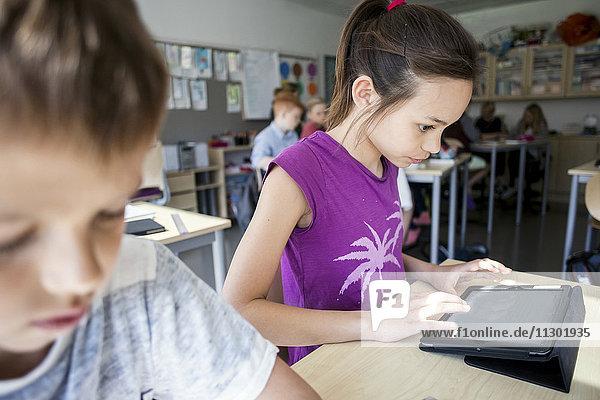 Mädchen sitzend von einem Jungen während der Benutzung des digitalen Tabletts im Klassenzimmer