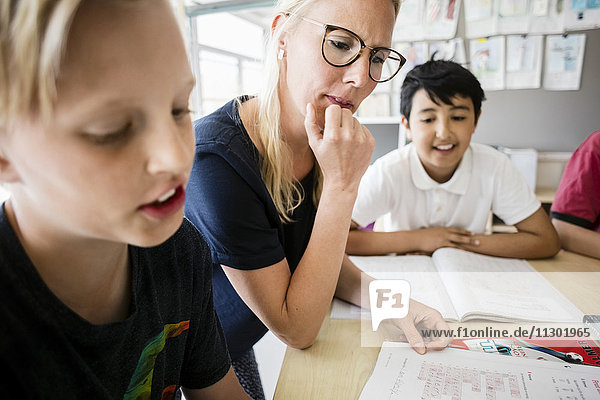 Lehrer und Schüler beim Lesen aus dem Buch im Klassenzimmer