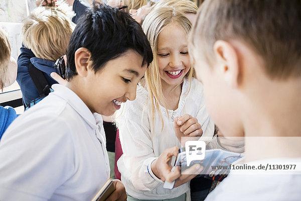 Fröhliche Schulkinder mit dem Handy im Flur