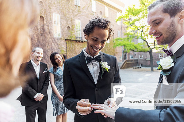 Schwules Paar tauscht Ringe während der Hochzeitszeremonie aus