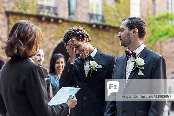 Schwuler Mann sieht schüchternen Partner an  während er während der Hochzeitszeremonie vor dem Priester steht.