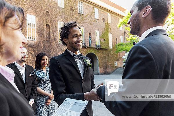 Priester und Freunde beim Anblick eines schwulen Paares bei der Hochzeitszeremonie