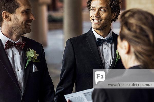 Rückansicht des Priesters vor dem glücklichen schwulen Paar