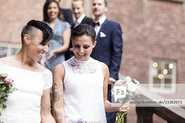 Low-Winkel-Ansicht des lesbischen Paares gegen Freunde im Hintergrund