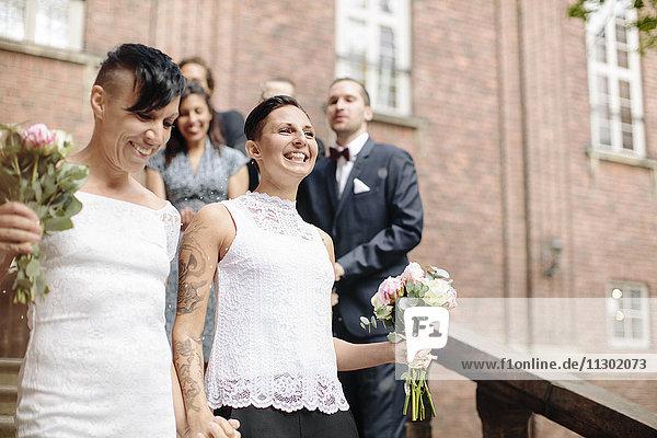 Flachwinkelansicht des glücklichen lesbischen Paares auf der Treppe mit Gästen im Hintergrund