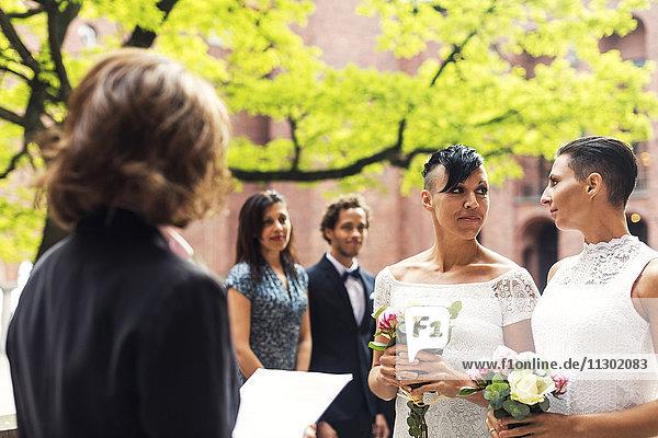 Lesbisches Paar  das sich ansieht  während der Priester im Vordergrund steht.