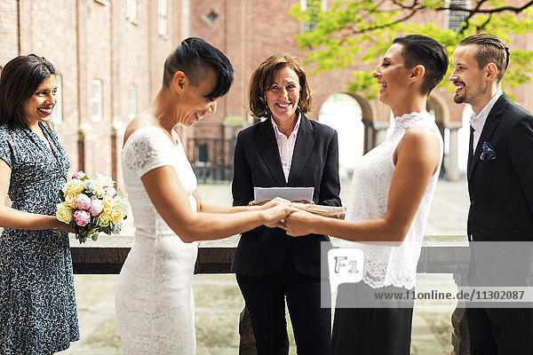 Priester und Gäste beim Anblick eines fröhlichen lesbischen Paares  das Händchen hält