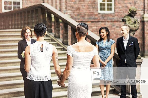 Rückansicht eines lesbischen Paares vor einer Priesterin