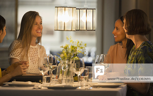 Lächelnde Freundinnen beim Essen und Trinken von Wein am Restauranttisch