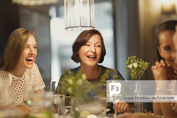 Laughing women friends dining and talking at restaurant table