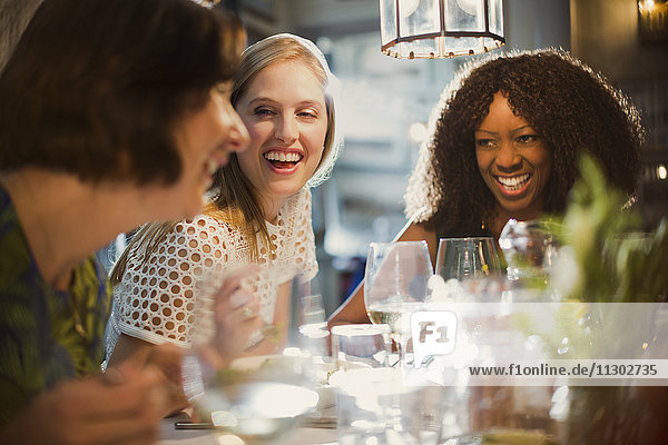 Laughing women friends talking and dining at restaurant table
